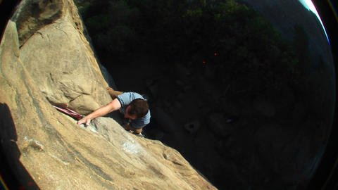 Fish-eye shot of a rock climber climbing up cliff face Stock Video Footage