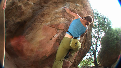 Fish-eye shot of a woman climbing a rock wall Footage