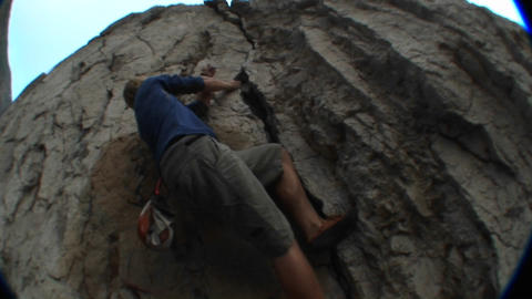 Following-shot of a rock climber scaling a cliff face Stock Video Footage