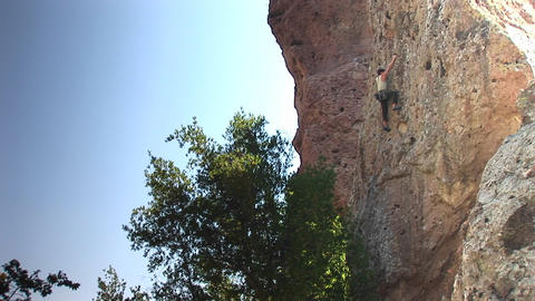 Long-shot of a rock climber scaling up a cliff face Footage