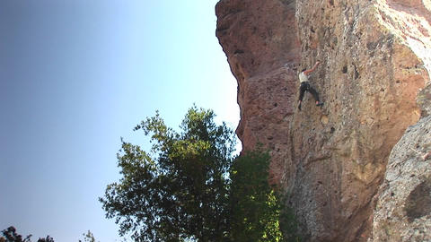 Long-shot of a rock climber scaling up a cliff face Stock Video Footage