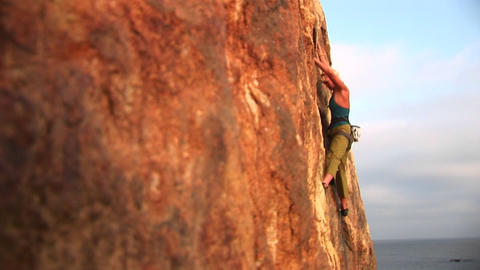 Pan-right of a rock climber attempting to climb a cliff... Stock Video Footage