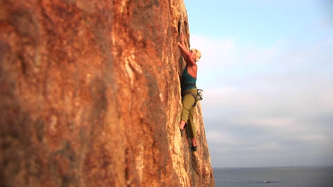 Pan-right of a rock climber attempting to climb a cliff wall over the Pacific Ocean Live Action