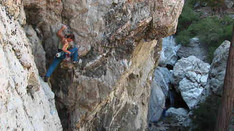 Long-shot of a rock climber rearranging her carabineers to climb a cliff wall Footage