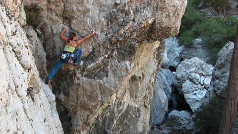 Long-shot of a rock climber rearranging her carabineers... Stock Video Footage