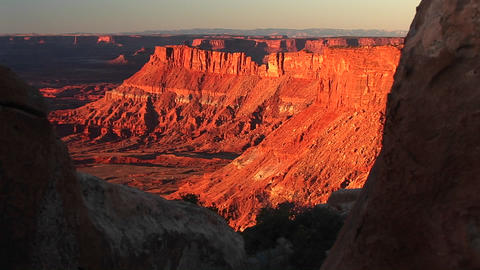 Medium-shot of buttes being bathed in the orange sunset glow at Canyonlands National Park, Utah Footage