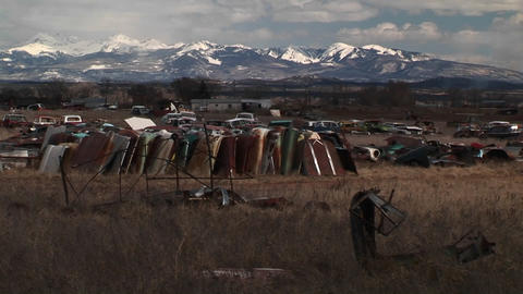 Medium-shot of a car junkyard in front of the scenic Rocky Mountains Footage