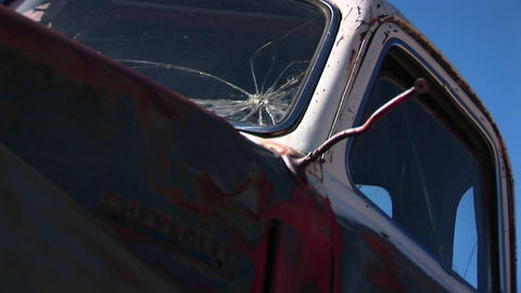 Close-up of rusted pickup truck cab with broken windows discarded and littering the Utah desert Footage