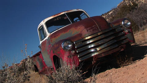 Medium shot of an old rusted pickup in the desert Footage