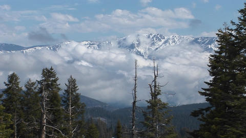 Wide shot of peaks covered with snow amongst clouds in Kings Canyon National Park Footage