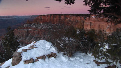 Wide shot of Grand Canyon National Park with foreground of cliffs edge and snow-covered rocks, shrub Footage