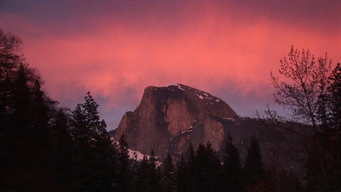 Medium wide shot of Yosemite's Half-Dome with fiery sky in background Footage
