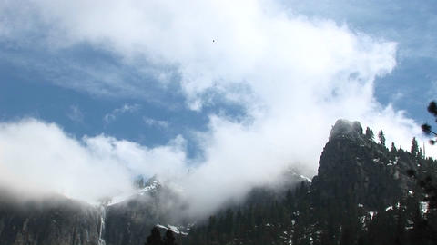 Medium-shot of Yosemite mountains being shrouded by low clouds Footage