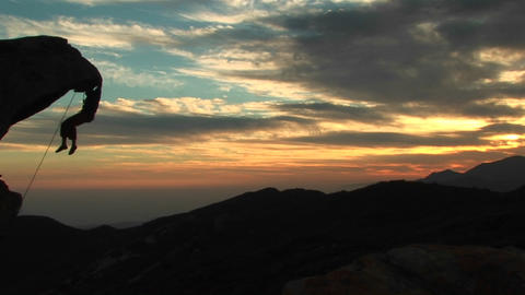 Pan-left of a silhouetted rock-climber hanging from an overhanging rock face with California sunset Footage