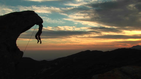 Pan-left of a silhouetted rock-climber hanging from an... Stock Video Footage