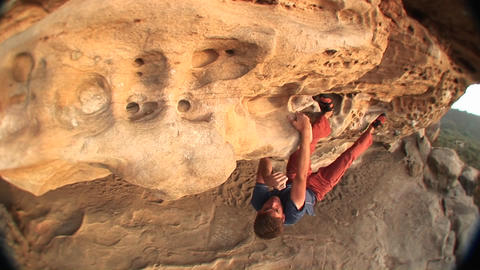 Fish-eye of a rock-climber making his way along the top... Stock Video Footage