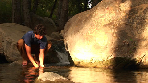 Medium-shot of a hiker washing his face in a mountain pool Footage