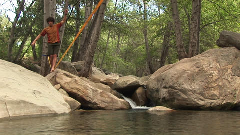 Jib-up of a young man slacklining across a placid... Stock Video Footage