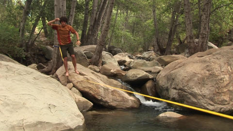 Jib-up of a young man slacklining across a placid swimming hole Footage