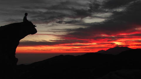 Medium-shot Of A Solitary Person Sitting On The Top Of A Rock-face Watching A Fiery Sunset stock footage