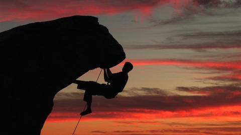 Medium-shot of a silhouetted climber hanging from an... Stock Video Footage