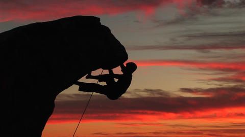 Medium-shot of a silhouetted climber hanging from an overhang rock face with a beautiful California Live Action