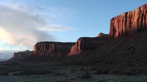 Medium-shot of reflected sunset light on sheer cliff... Stock Video Footage