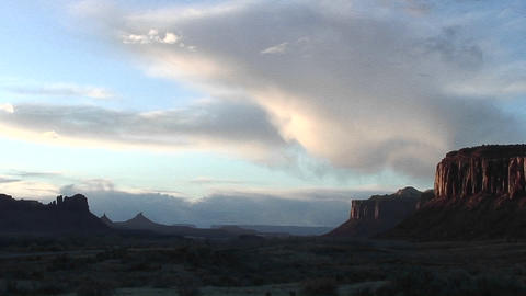 Medium-shot of a butte being illuminated by light of the setting sun near Moab, Utah Live Action