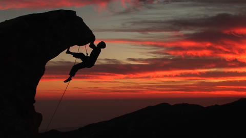 A man climbs a rugged peak in silhouette at sunset Stock Video Footage