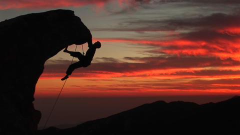 A man climbs a rugged peak in silhouette at sunset Footage