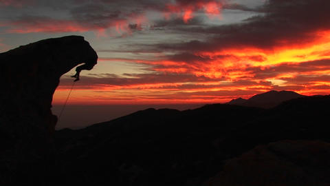 Medium-shot of a silhouetted climber hanging from an overhanging rock Footage