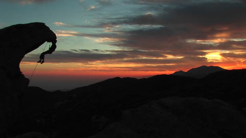 Medium-shot of a rock-climber silhouetted by the... Stock Video Footage