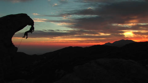 Medium-shot of a rock-climber silhouetted by the setting-sun hanging from an rock overhang Footage