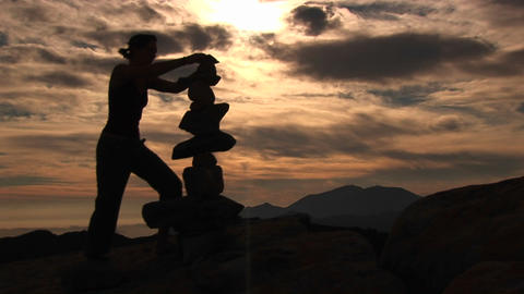 Medium-shot of a silhouetted woman stacking rocks on a... Stock Video Footage