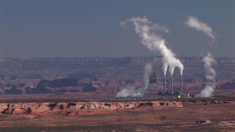 Medium-shot of a factory in the Arizona Desert disgorging pollution Live Action