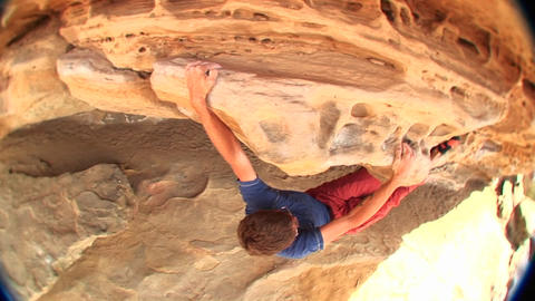 Fish-eye of a young rock-climber gingerly maneuvering his way along a rock-face Footage