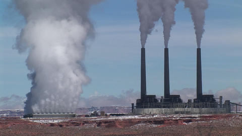 Medium-shot of a factory releasing pollution in the Arizona Desert Footage