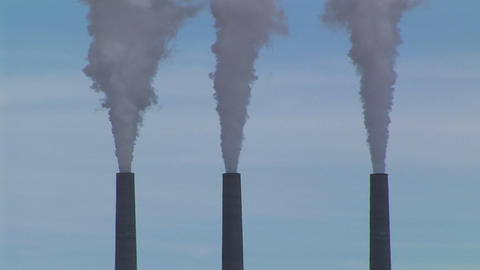 Medium-shot of three smokestacks belching fumes in an... Stock Video Footage