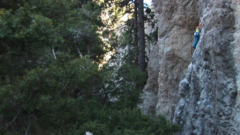 Medium-shot of a climber making her way up a granite cliff face Footage
