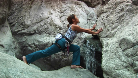 Medium-shot of a woman doing stretches next to a small waterfall on a granite rock-face Live Action