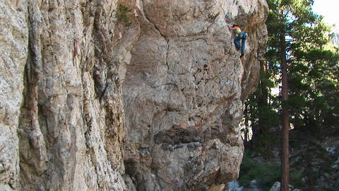 Pan-up of a rock-climber laboriously climbing a granite rock-face Footage