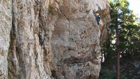 Pan-up of a rock-climber laboriously climbing a granite... Stock Video Footage