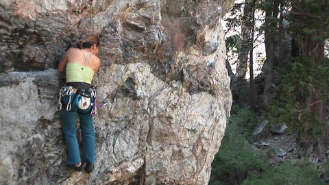 Medium-shot of a rock-climber making her way up a granite cliff face Live Action