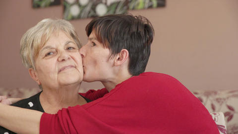 mother and daughter love: young woman cover her mother with kisses Footage