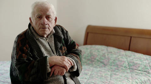 Pensioner leaning on his cane, seated on a bed looks at the camera Footage