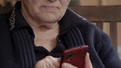 Detail of old woman hands using a smartphone Live Action