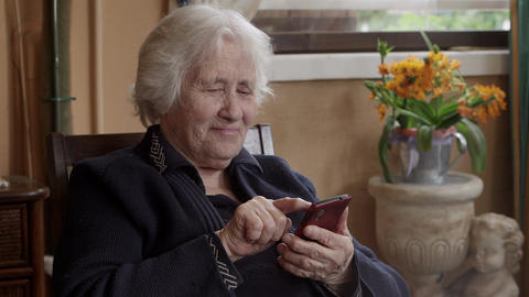 Happy grandmother uses a smarthone Footage