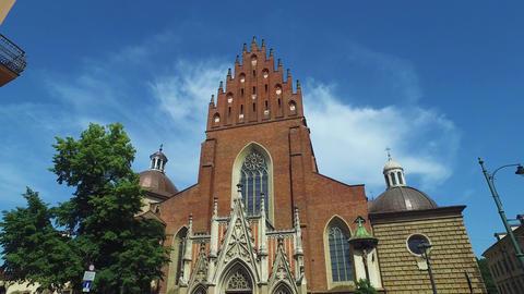 Krakow, Poland. Exterior of Holy Trinity Church Basilica Under Summer Sky Live Action