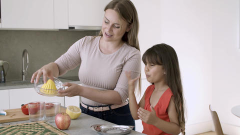 Cheerful mom and little daughter squeezing lemon Live Action