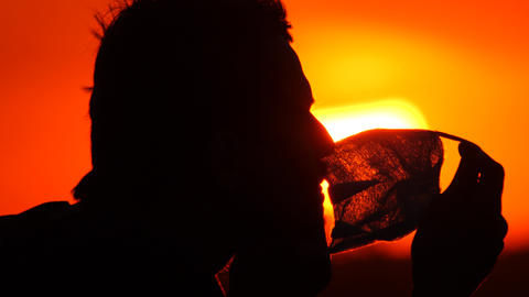Silhouette profile of a young man in a mask. Male removes a protective Live Action